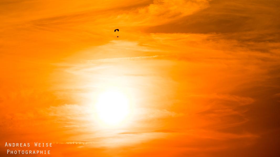 Gleitschirm vor der untergehenden Sonne